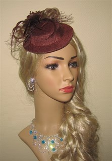 Коричневая плетеная шляпка с бантом и перьями.